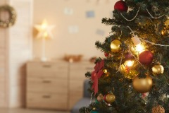 Background image of beautiful Christmas tree decorated with golden baulbs in cozy home interior, copy space
