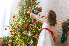 girl is decorating Christmas tree