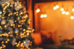 Home background. Reading corner near the fireplace and Christmas tree with gifts. Blurred.