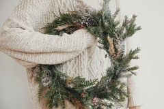 Christmas rustic wreath. Hipster girl in stylish white sweater holding rural christmas wreath with fir branches, berries, pine cones and herbs in room. Happy holidays